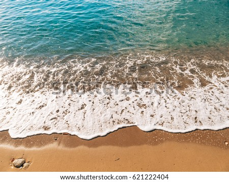 Sandy beach and waves, close-up. Texture of sand and water. Picture for the postcard. Vacation at sea. Advertising of the sea.