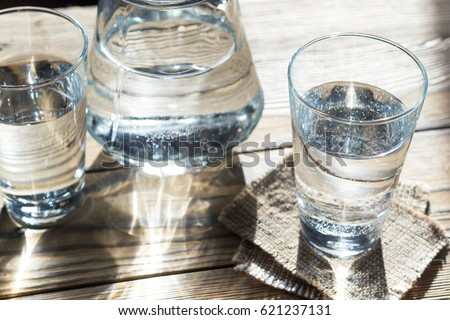 Glass of water on a wooden table. Selective focus. Shallow DOF. With light effects. #621237131