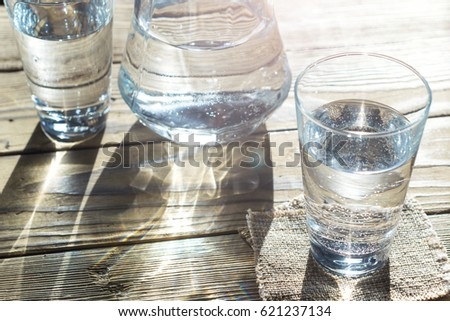 Glass of water on a wooden table. Selective focus. Shallow DOF. With light effects. #621237134