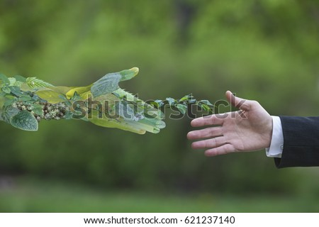 Hand of a businessman reach out towards hand of the nature Royalty-Free Stock Photo #621237140