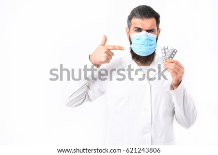Bearded man, long beard. Brutal caucasian doctor or unshaven hipster, postgraduate student in mask and medical gown holding pills isolated on white studio background. Medicine concept #621243806