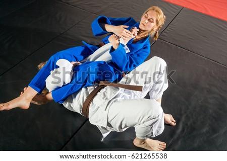 Judo, Jiu Jitsu. Two women are fighting on tatami. Blue and white kimano. Painful reception. Ground floor Royalty-Free Stock Photo #621265538
