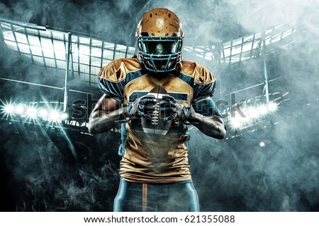 American football sportsman player on stadium with lights on background Royalty-Free Stock Photo #621355088
