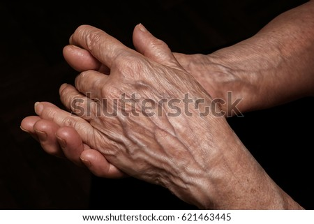 Folded senior woman wrinkled hands close up. On abstract background, clipping path included. Old age, age problems, poverty and loneliness theme #621463445