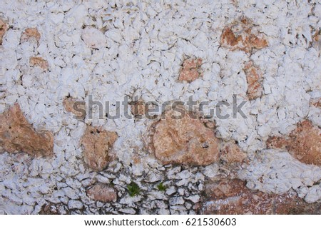 Very rustic and rough textured exterior wall made of stone and white stucco in colonial Mexican city #621530603