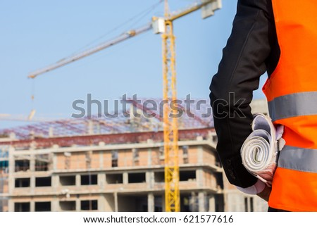 Young engineer wearing a orange shirt stands holding a blueprint while standing at a building under construction with a crane. #621577616
