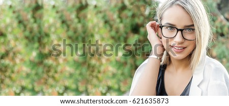 portrait of a young woman, blonde, glasses, outdoors in the park #621635873