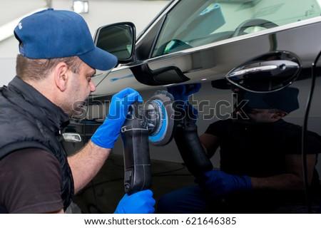 A man polishes a black car with a polishing machine #621646385