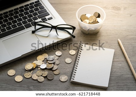blank notebook with pencil, glasses, laptop and thai coins on wooden table #621718448