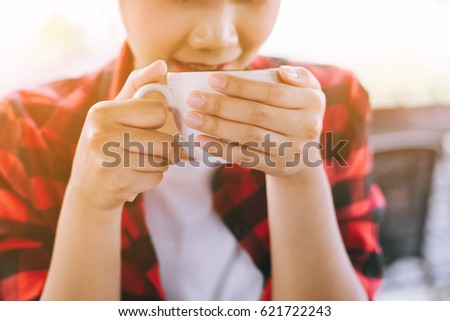 woman holding hot cup and blowing on it #621722243