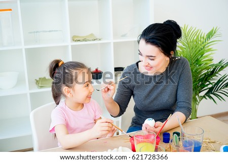 Mother and daughter painting eggs #621728366