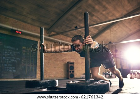 Strong man pushing heavy bogie with weight disks. Horizontal indoors shot #621761342