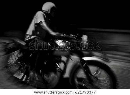 Motion blur. Monochrome. Men riding a vintage motorcycle at night. #621798377