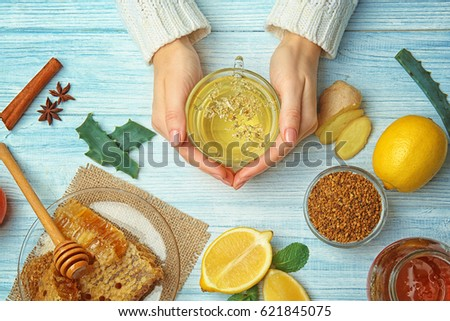 Female hands holding cup of herbal tea on wooden background Royalty-Free Stock Photo #621845075