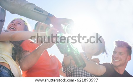 Happy friends cheering and celebrating at bbq party with beer outdoor against sun light - Young trendy people having fun laughing together - Focus on bottles - Youth and summer concept - Warm filter