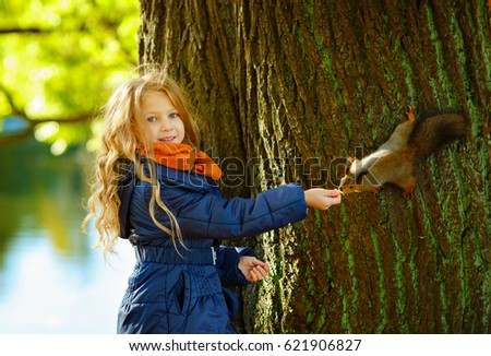 A little girl with long hair feeds a squirrel in an open forest and smiles #621906827