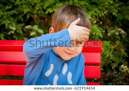 Shy but curious little Caucasian child peeking from under his hand stock image.