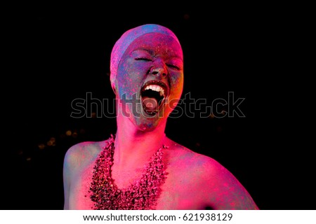 A fashion model poses for the camera in front of  a black background. She has been blasted with various powder pigment colors on her face and body. #621938129
