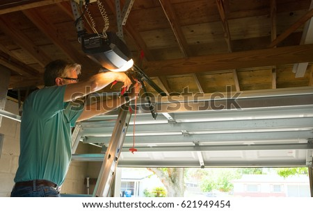 Professional automatic garage door opener repair service technician man working on a ladder at a home residential location making adjustments and fixing it while installing it. Royalty-Free Stock Photo #621949454