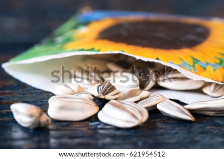 Sunflower Seeds Spilled from a Seed Packet Royalty-Free Stock Photo #621954512