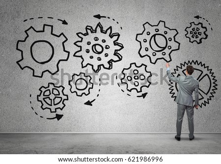 Businessman standing with back and drawing concept of teamwork and cooperation #621986996