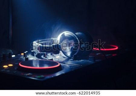 DJ Spinning, Mixing, and Scratching in a Night Club, Hands of dj tweak various track controls on dj's deck, strobe lights and fog, selective focus, close up. Dj Music club life concept Royalty-Free Stock Photo #622014935