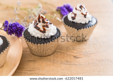 chocolate cup cake with whipped cream on table #622057481
