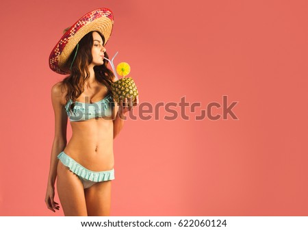 young beautiful woman in bikini and sombrero drinking exotic tropic cocktail isolated on pink background