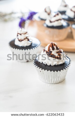 chocolate cup cake with whipped cream on table #622063433