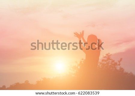 Silhouette of woman praying over beautiful sky background #622083539