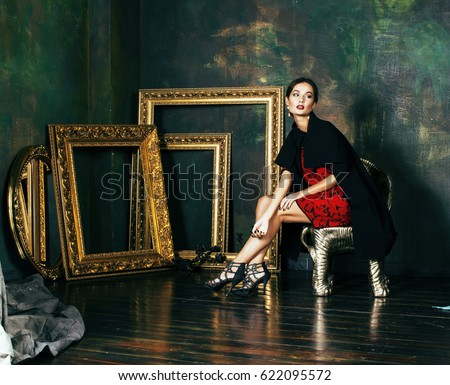 beauty rich brunette woman in luxury interior near empty frames, wearing fashion clothes, lifestyle pretty real people concept #622095572