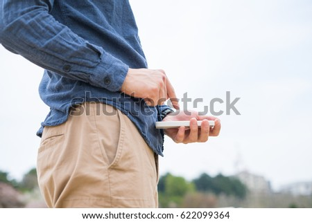 Man holding a smartphone #622099364