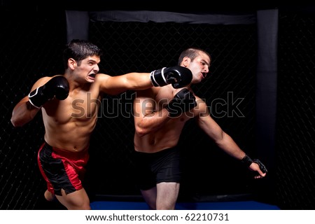 Mixed martial artists fighting - punching Royalty-Free Stock Photo #62210731
