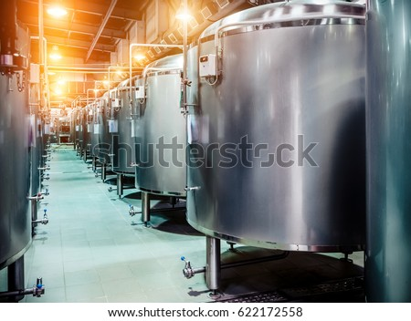 Modern Beer Factory. Rows of steel tanks for beer fermentation and maturation. Spot light effect #622172558