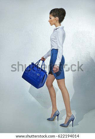 Pretty woman in white blouse and blue skirt with blue bag #622194014