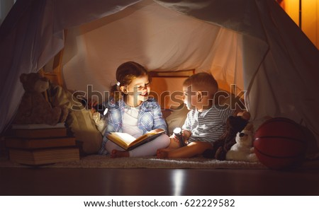 children boy and girl reading book with flashlight in  tent at night #622229582