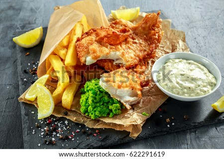 British Traditional Fish and chips with mashed peas, tartar sauce on crumpled paper. Royalty-Free Stock Photo #622291619