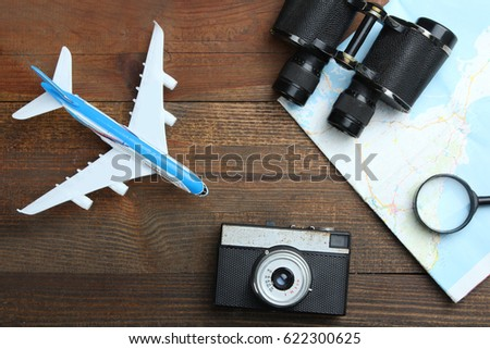 Toy airplane, map, binoculars, camera and magnifying glass on a wooden background