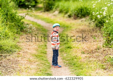 Day view of boy on footpath summer park. Countryside #622329905
