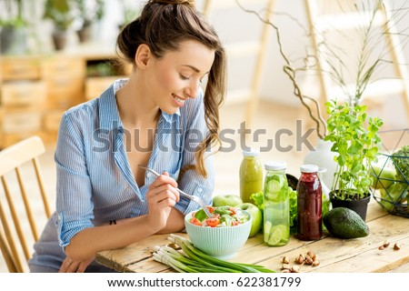 Young and happy woman eating healthy salad sitting on the table with green fresh ingredients indoors #622381799