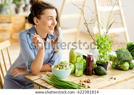 Young and happy woman eating healthy salad sitting on the table with green fresh ingredients indoors Royalty-Free Stock Photo #622381814
