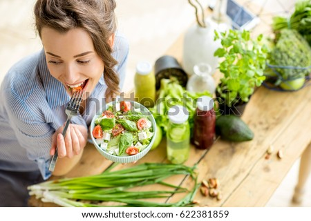 Young and happy woman eating healthy salad sitting on the table with green fresh ingredients indoors Royalty-Free Stock Photo #622381859