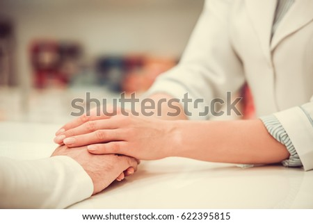 Cropped image of pharmacist holding a client's hand and supporting him, in pharmacy #622395815