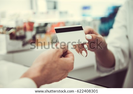 At the pharmacy. Cropped image of young female pharmacist taking a credit card from a client while working at the cash desk #622408301