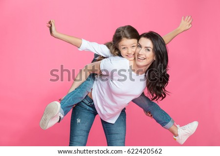 Happy mother piggybacking adorable little daughter smiling at camera Royalty-Free Stock Photo #622420562