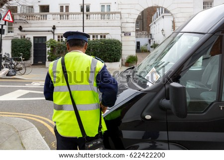 LONDON, UK - MARCH 17, 2017; Officer issues parking ticket fine  #622422200