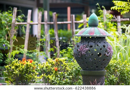 The marvelous exterior of the backyard in the house on which a vase or a lamp in the form of an emerald-colored sculpture is represented, green plants with flowers and a wooden fence in the background #622438886