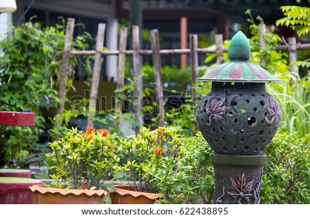 A decorative composition in the backyard of the garden, consisting of a lamp made in the form of sculpture, pots with plants and flowers and a wooden fence with a palisade in the background (close) #622438895