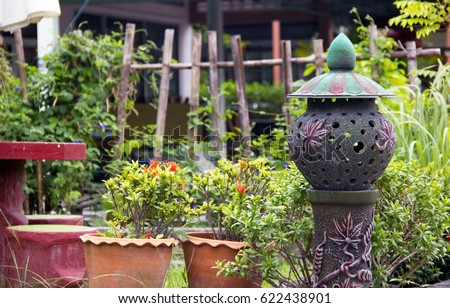 A decorative composition in the backyard of the garden, consisting of a lamp made in the form of sculpture, pots with plants and flowers and a wooden fence with a palisade in the background #622438901