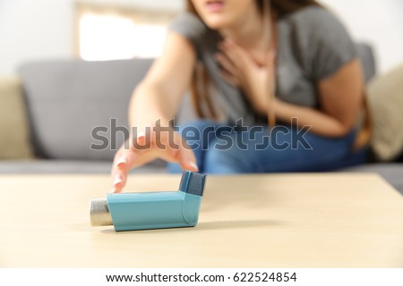 Girl suffering asthma attack reaching inhaler sitting on a couch in the living room at home Royalty-Free Stock Photo #622524854